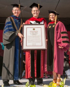 Fr. Sean Carroll, S.J. holding the honorary doctorate from Santa Clara University, with SCU President Fr. Michael Engh, S.J. (l.) and Dr. Kristin Heyer, associate professor of religious studies at SCU (r.).  Photo by Charles Barry/Santa Clara University.
