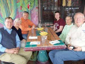 West Cosgrove (in orange shirt), Ed Lorenz (far left) and immersion participants from Alma College await lunch at a local eatery.