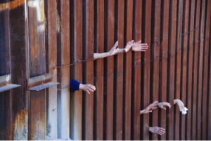 Hands reaching across the border wall. Photo by Christine Krikliwy, Voice of the Poor, Tucson.