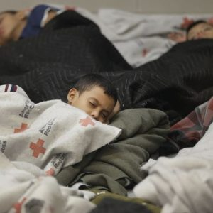 A young boy sleeps at one of the temporary detention centers. credit:  Michael Wallace AZ Red Cross