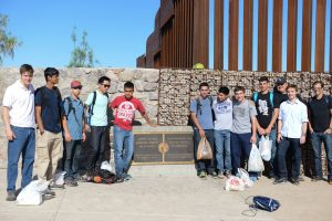 Students from Bellarmine College Preparatory pose by the border fence with Chris Boitano of the KBI (far left) and their teachers Joe Cussen (third from right) and Chris Cozort (far right). Bellarmine students from left to right are: Ashwin Mukund, Rudy Diaz, Matthew Kim, Ramon Garcia-Gomez, Tyler Edgerle, Emilio Flamenco, Nick Culine, David Dalton, Ryan Demo. Photo by Ryan Demo.