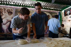 Tyler Edgerle, right, with classmate Nick Culine, helps prep for lunch at the KBI Outreach Center. Photo by Ryan Demo.