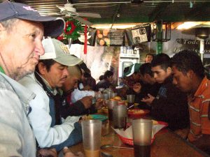 The Real Deal: Migrants gather at the KBI comedor to share a meal in a spirit of gratitude for the gifts of safety, nourishment and companionship. Photo by Roxane Ramos.