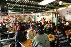 The migrants gather with KBI staff and volunteers before the morning meal. Photo by Andrea Cauthen.
