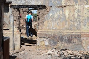 A Bellarmine student inspects the ruins of a house near the border where migrants have taken shelter.
