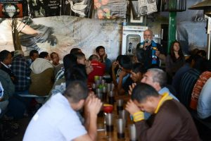 Father Pete speaks with migrants at the KBI comedor.