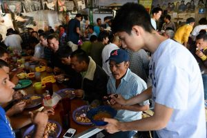 Bellarmine students serve the migrants who have gathered for a meal.