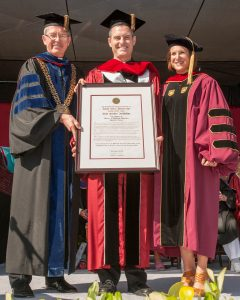 Fr. Sean Carroll, S.J., holding the honorary doctorate from Santa Clara University, with SCU President Fr. Michael Engh, S.J. (l.) and Dr. Kristin Heyer, professor of religious studies at SCU (r.). Photo by Charles Barry/Santa Clara University.