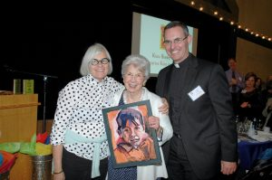 Jean Wallace, recipient of the Pope Francis Award, holds the Migrant Portrait she received in acknowledgement. With the portrait's artist, Pamela Hoffmeister, and Father Sean.