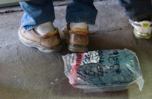 Undocumented migrants are deported with what they can fit in the small plastic bag provided by the U.S. Department of Homeland Security. These bags mark the migrants as easy targets for criminals at the border. Photograph by Larry Hanelin.