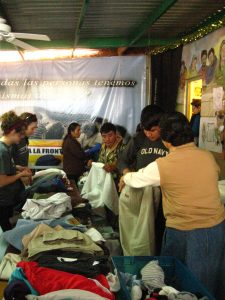 KBI staff and volunteers help the migrants at the comedor select the garments they need.