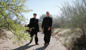 Fr. Carroll (right) walks with Archbishop John C. Wester of Santa Fe in the Arizona desert in 2014. Fr. Carroll took a group of bishops on a hike north of Nogales where migrants often cross into the United States. (CNS photo/Nancy Wiechec)