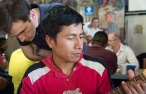Thomas Flowers, S.J. listens to a migrant share a song after the meal. Photo by Larry Hanelin, courtesy of the Jesuit Conference.