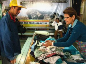 After the morning meal, volunteer Lourdes Monroy distributes clothing at the comedor. Photo by Roxane Ramos.