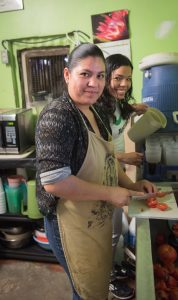 Mariana Serrano, a KBI staff person, and Bernie, a student from the ITESO, the Jesuit university in Guadalajara, Jalisco, prepare the morning meal. Photo by Larry Hanelin.