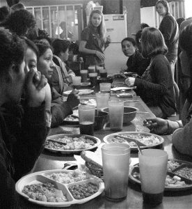 Migrants share food and stories at the comedor. Photo by Roxane Ramos.