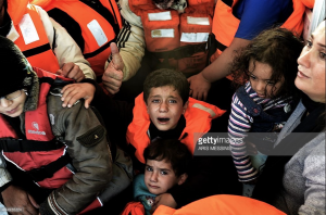 Syrian Kurdish refugees are rescued by Greek fisherman as the boat they had boarded sinks off the Greek island of Lesbos after crossing the Aegean Sea from Turkey on October 30, 2015. Photo by ARIS MESSINIS/AFP/Getty Images.
