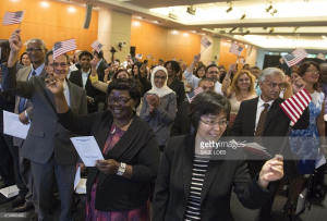 Many Faces, Many Stories: People celebrate after taking the citizenship oath to become U.S. citizens during a naturalization ceremony at the US Patent and Trademark Office in Alexandria, Virginia, May 28, 2015. Photo by SAUL LOEB/AFP/Getty Images.