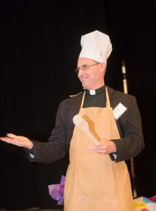 Father Sean lends some levity to the proceedings, donning a chef's hat and apron for the most popular auction item, a gourmet meal prepared by Father Sean and Father Pete Neeley at the Jesuit Residence in Nogales, Arizona