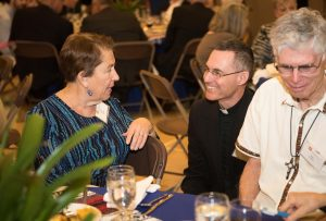 Father Sean, here with Barb and Ray Daoust, visited each table of KBI supporters throughout the evening.