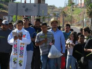 Father Samuel Lozano de los Santos, S.J. KBI Director of Programs in Mexico, prays with those gathered outside the comedor on Palm Sunday.