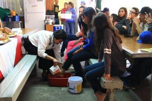 On Holy Thursday, Sister Alicia Guevara Pérez, M.E., one of the KBI's Migrant Aid Coordinators, washes the feet of a migrant visitor to the comedor.