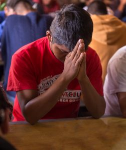 Before each meal at the comedor, everyone prays together. Photo by Larry Hanelin.
