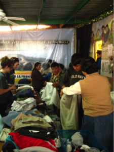 KBI staff and volunteers help the migrants at the comedor select the garments they need. Photo by Roxane Ramos.