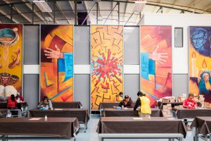 Paintings of outstretched hands in a large dining hall.