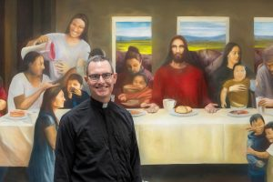 Fr. Sean stands in front of a mural of Jesus at the comedor and smiles.